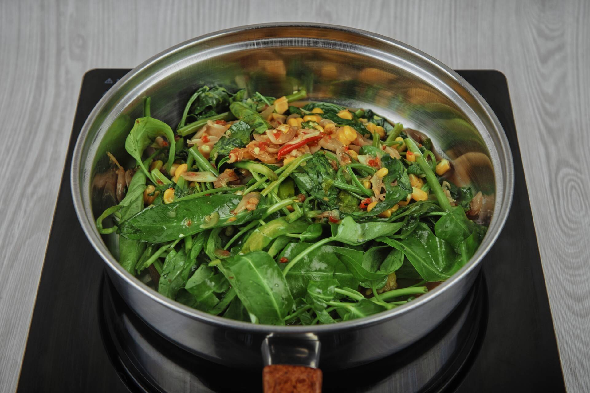 Add the water spinach and sweet corn